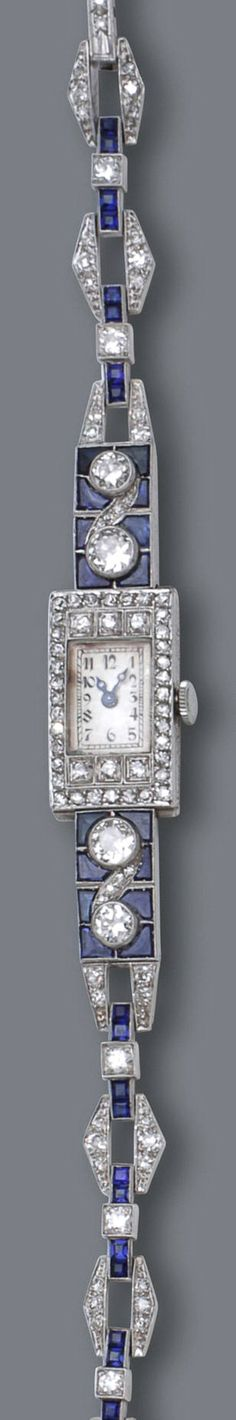 An art deco diamond, sapphire and synthetic sapphire watch, Omega, circa 1925 the rectangular silvered dial with black Arabic numerals and blued steel hands within an old European and single-cut diamond case, completed by an openwork bracelet of square and calibré-cut sapphires and synthetic sapphires, further accented by old European-cut diamonds