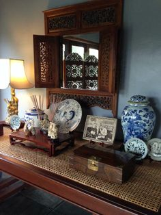 Asian interiors - old Philippine table with Chinese  and Vietnamese blue and white porcelain, Thai mirror, Korean chest, white cinnabar from Mom in law and my Grandmother's brass lampshade