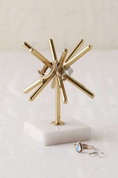 Decor/accessories - Gold sunburst design ring stand with white marble base. Complete with 5 rods for keeping your rings safe + secure. Great decor piece, too!