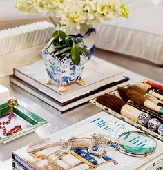 If you have a square coffee table, try stacking two diagonal corners with books and filling the rest of your space with artful objects. House Beautiful