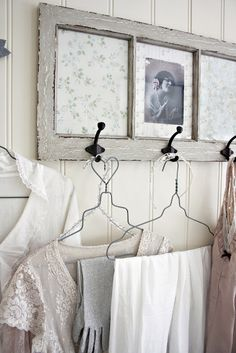 ~ old window hung horizontally..behind glass panes is a floral design and a old photograph..below are hooks...to hold clothes on hangers