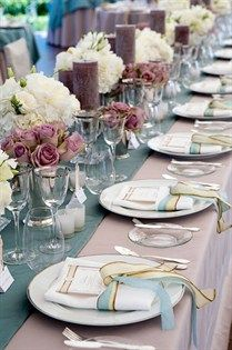Long tables feature mauve tablecloths with blue runners and dozens of candles and flowers.
