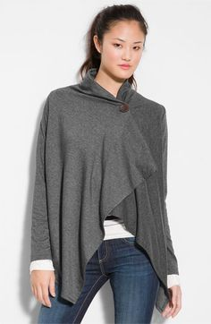 A dramatic, wrap-style cardi is cut with an asymmetrical hem and secured with a single button at the neckline.