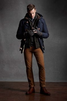 Shop this look on Lookastic: http://lookastic.com/men/looks/brogue-boots-chinos-scarf-henley-sweater-gloves-gilet-duffle-coat/6559 — Brown Leather Brogue Boots — Brown Chinos — Navy and White Scarf — Charcoal Henley Sweater — Charcoal Wool Gloves — Dark Brown Quilted Gilet — Navy Duffle Coat