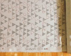 "Dots and lines and empty spaces make triangles appear and disappear across  the width of fabric. Printed in deep brown CLAY + RUST on sand colored  linen, the BETU design is a great geometric texture for a variety of design  palettes.  Content: 100% Linen Fabric Width: 52"" Repeat Size: 12.6""H x 18""W  For orders of more than 10 yards or to request a sample swatch please  email info@brookperdigontextiles.com"
