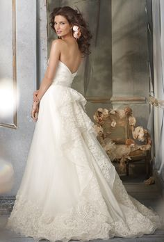 Brides: Jim Hjelm. Ivory Silk Organza A-line formal bridal gown, strapless draped bodice, natural waist with Ivory ribbon and floral detail, embroidered cascade back and hem, chapel train.