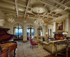 Ultra luxurious living room features fine detailed ceiling with crystalline chandeliers hanging over dark hardwood flooring with twin beige sofas and carved red chair, before immense dark marble fireplace and grand piano.