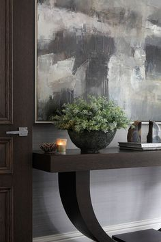 espresso brown wood console table | foyer design ideas | home staging ideas | blue white grey taupe abstract paint | nickel square door handle | stained interior doors | door moulding | grass cloth wallpaper