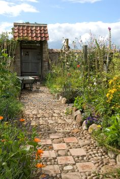 Garden path of stones, pebbles & tiles leading to garden gate door, with wheelbarrow, chicken, vegetable and flower garden borders | Plant & Flower Stock Photography: GardenPhotos.com