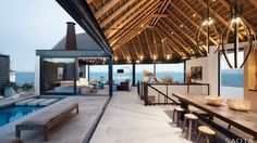 The beautiful thatched roof, a classic beach house style with a modern take in this instance, is supported by a perimeter I-beam and stands in natural contrast with the more industrial granite flooring.
