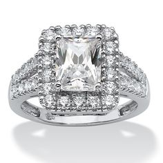 A virtually glowing emerald-cut cz is surrounded by round cubic zirconia stones both around the main stone and along the-0OcsQVTK