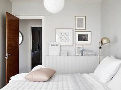 Grey walls, brass reading lamp, gallery wall and a Hay polygon quilt in a swedish bedroom. Stadshem / Jonas Berg.