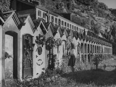 Lady Visiting an Unkept Cemetery Which Shows a Row of Vertical Tombs in the Shape of Houses