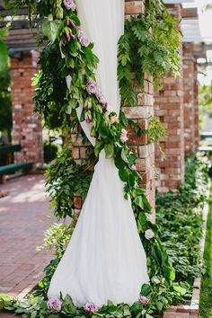 Stunning Draped Ceremony Backdrop Lined with Flowers ~ detail of garland lining curtains