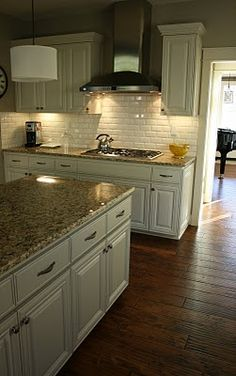 antique white cabinets, brown granite, hardwood floors