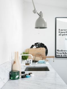 white fixture, marble counter, marble backsplash, pendant light