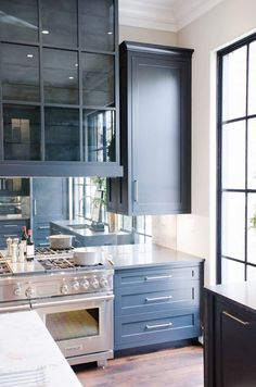 In the Atlanta Holiday Home, an antiqued mirror was installed as the kitchen backsplash. This trick works fantastically in small galley…