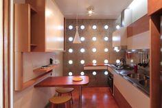 Na cozinha, a luz do dia entra pelas pequenas janelas basculantes. Há harmonia entre as linhas circulares na parede e a marcenaria de cantos arredondados.
