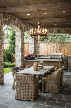 Rustic wicker chairs and vintage table with grill area on this farmhouse elegant veranda
