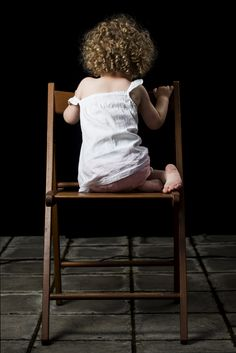 Little girl sitting on wooden chair with a back turned towards us