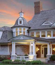 "shingle style - white-trimmed shingle exterior (in aged grey or ""natural"" brown), eyebrow window, turret, pigeon cupola, divided-lite (15 over 1) windows, multiple columns at a corner"
