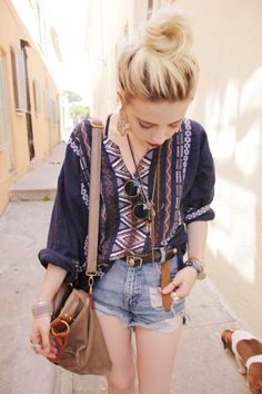 High waisted denim shorts. Patterned button down top. Circular sunglasses. Blonde. Slouch bag.