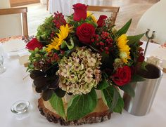 Yellow Sunflowers, Autumnal Low Wedding Table Centre Arrangement | Perfect for an autumn wedding using a combination of ruby reds roses, dahlia, green foliage and Hydrangeas & natural tones and yellow sunflowers | Triangle Nursery Ltd Wholesale Flowers & Accessories for Everyone!