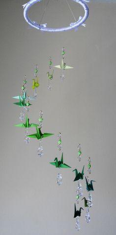 Móbiles de Tsuru com 12 pássaros em papel japonês, com mini estrelas, aro de acrílico encapado com fita de seda e laços, pingentes e miçangas em acrílico - Tsuru em tonalidades de verde. Dimensões - 65 cm de altura por 20 cm de largura.