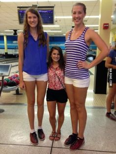 Two tallest volleyball players and shortest cheerleader