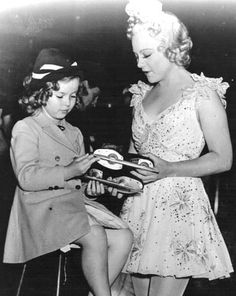 Shirley Temple taking a look at Sonja Henie's skates.