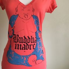 """NWOT SpEnglish Budda Madre Tee If you love puns and Spanish, then you'll love this shirt. I am torn over letting it go, but sadly, it will never fit me and that makes me cry """"¡Puta madre!"""" NWOT Bright mango color with turquoise stitching. Size medium, but will best fit a small (mannequin is size 4 for reference). No trades or Paypal. Reasonable offers are appreciated. SpEnglish Tops Tees - Short Sleeve"""