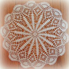 This beautiful doily features a multi-spoked center surrounded by open-worked diamonds. Lovely fans form a scalloped edge along the outside. Worked in ecru/natural thread, and measuring a generous 18-3/4 across, it would make a lovely addition to your home or the home of a friend.