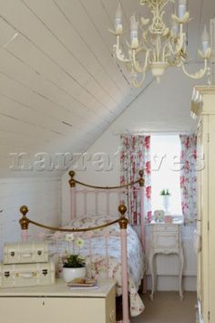 Single bed with brass bed knobs in attic bedroom with coordinating curtains and bedspread