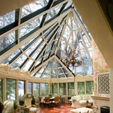 An atrium-style glass ceiling floods this conservatory with natural light. Floor-to-ceiling windows also provide optimum lake  views . | HGTV FrontDoor