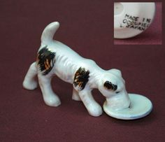 """Occupied Japan Cute dog drinking milk or water. It stands 1"""" high and 4 1/2"""" long. It was probably made in one mold. It is highly likely made in Seto, Aichi Prefecture, Japan. From Shoko Tanaka Collection"""