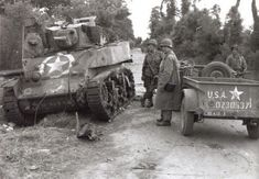 """This intersection, several mile North of Carentan, originally got it's name from the fact that on 7 June, 1944, a American light tank (M-5) of Company 'D', 70th Tank Battalion, was knocked-out nearly in front of the large house and sat there for days afterward. The burned body of the tank commander could still be seen in the turret, and soldiers started to use it as a reference point, saying, """"go to the corner where the dead man is in the tank"""". This was soon shortened to 'Dead Man's…"""