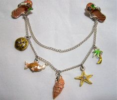 Vintage enamel beach vacation sweater clip Clips are rhinestone and enamel flip flops With dangling charms palm tree, starfish, shell, fish and sand dollar. All are enamel some with rhinestones In beachy colors of pink, peach, and green Silver tone setting 6 3/4 inches long, each