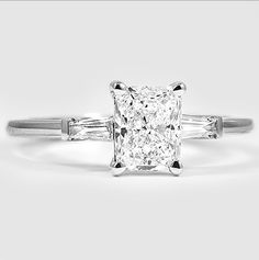 Tapered channel-set baguette diamonds brilliantly frame the radiant cut diamond in this engagement ring.