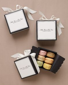 "Macaron Favors Clad in white grosgrain ribbon and black glassine, favor boxes—printed with ""Thank you for coming"" in French—hold pastel-hued macaroons by Mad Mac."