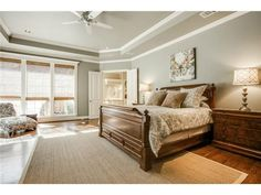 Comfortable, clean master bedroom // Wall of windows, crown molding, tray ceiling, hardwoods, gray walls