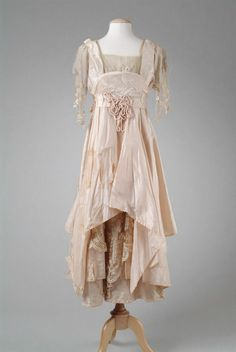 Dress:1914  Designer:Whitey  Description:Pink silk taffeta evening gown with a pannier effect on the hip, and trimmed with machine embroidered net. Accented with cruched cording flower trim. Back