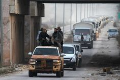 Rebel fighters escort a Syrian Arab Red Crescent aid convoy