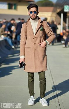 Shop this look on Lookastic:  http://lookastic.com/men/looks/sunglasses-turtleneck-pocket-square-overcoat-chinos-low-top-sneakers/8639  — Blue Sunglasses  — Beige Knit Turtleneck  — Green Print Pocket Square  — Camel Overcoat  — Olive Chinos  — White Low Top Sneakers