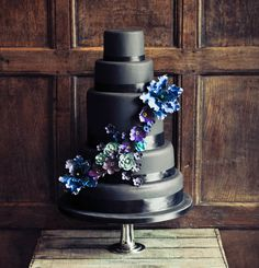 Black wedding cake with blue, purple and teal floral cascade. Different and stunning. Could also be nice for the groom if you change the flowers into some masculine accent.