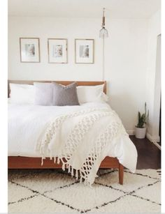 Minimalist monochromatic bedroom with Moroccan shag rug, pendant light and gray accent pillows.