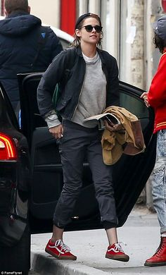 Day out: Kristen paired cropped trousers with a navy bomber jacket and a grey jumper ...