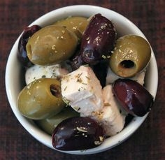 Marinated Olives with Feta Cheese  ¼ cup olive oil  2 Tbsp. red wine vinegar  2 Tbsp. crushed garlic  2 tsp. dried herbs  ¼ tsp freshly ground pepper  2 cups mixed green and black olives  1 cup diced feta cheese  In a large bowl, whisk together oil, vinegar, garlic, herbs and pepper. Add olives and feta; toss to coat. Store in an airtight container for at least 30 minutes before serving.