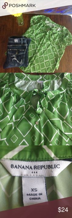 Banana Republic Top Super cute Banana Republic blouse. It is green and off-white with silver buttons. It has elasticized cap sleeves and a tie neck. Perfect for work or drinks with friends. 100% polyester. Size XS. Banana Republic Tops Blouses