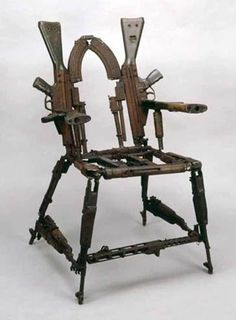 Man Cave gun chair. I would be epic if one of them on the arm rest actually fires.