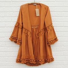 Dreamy rust tones pair with gorgeous fringe details on this duster. Designed with a draped open front, crochet inset details, and gorgeous fringe hem. Soft draped fit. The perfect bohemian addition to